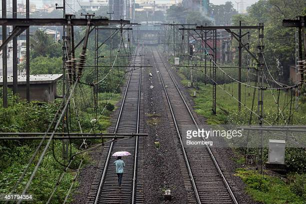A pedestrian holding an umbrella walks along rail tracks in Mumbai India on Friday July 4 2014 Indian Railways' annual budget is scheduled to be...