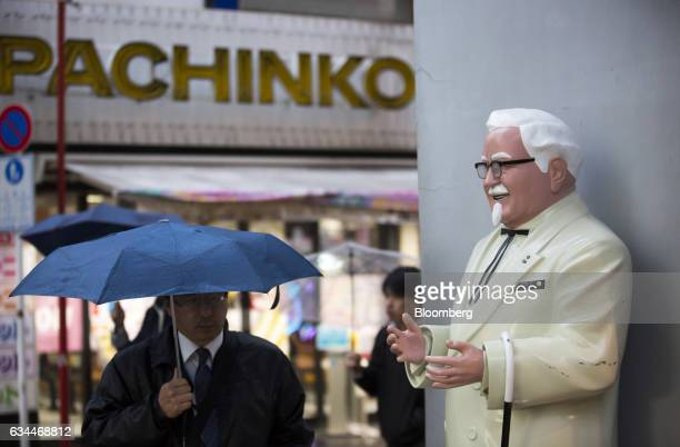 A pedestrian holding an umbrella walks near a statue of Colonel Harland Sanders the founder of Kentucky Fried Chicken outside a Kentucky Fried...