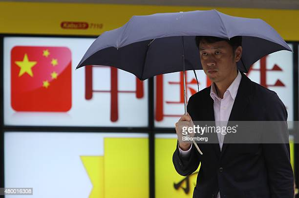 A pedestrian holding an umbrella walks past an electronic board displaying an advertisement of Chinese stocks outside a securities firm in Tokyo...