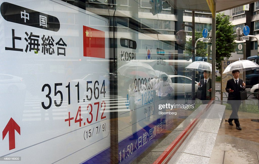 A pedestrian holding an umbrella walks past an electronic board displaying the Shanghai Composite Index outside a securities firm in Tokyo Japan on...