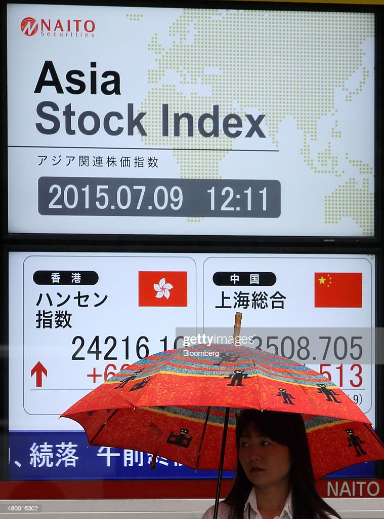 A pedestrian holding an umbrella walks past an electronic board displaying the Hang Seng Index bottom left and the Shanghai Composite Index bottom...