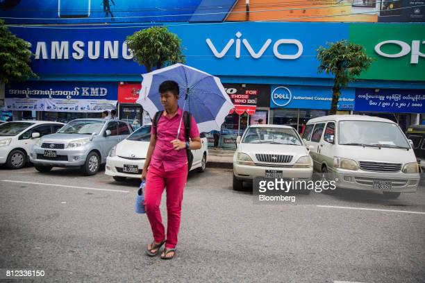A pedestrian holding an umbrella walks past stores and logos for Samsung Eletronics Co left Vivo Communication Technology Co center and Oppo...