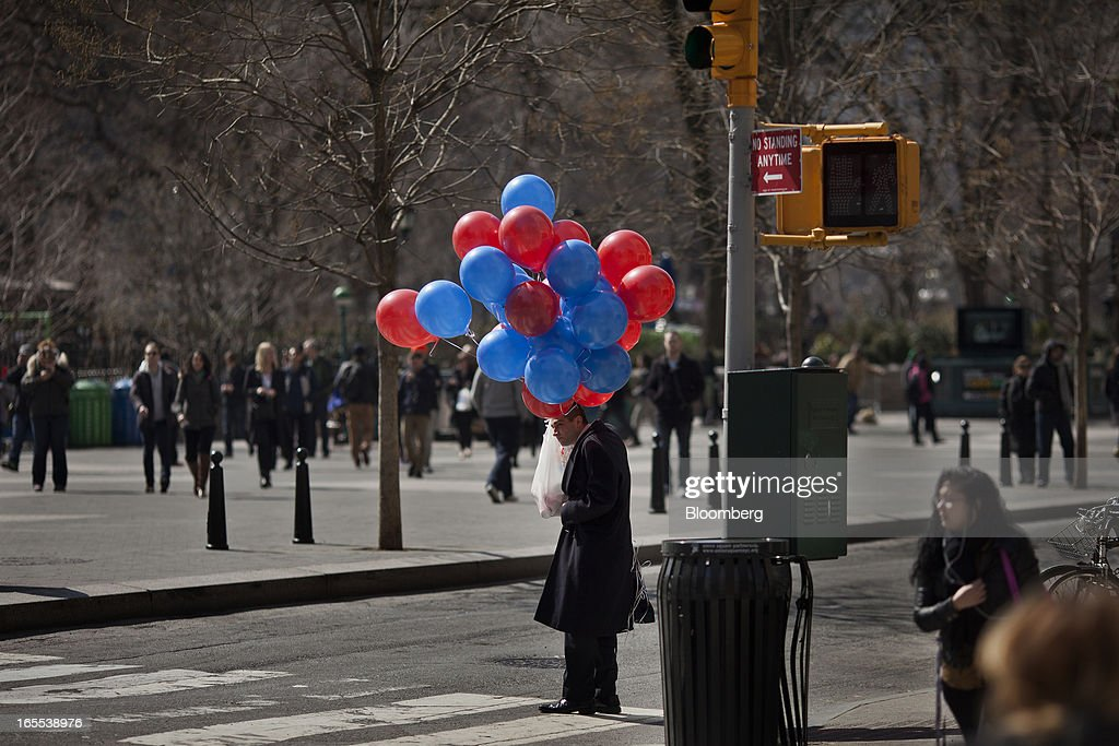 A pedestrian holds a shopping bag and balloons while walking through Union Square in New York, U.S., on Thursday, April 4, 2013. Confidence among U.S. consumers stabilized last week, stemming a pullback in sentiment that had threatened to check recent gains in spending. Photographer: Victor J. Blue/Bloomberg via Getty Images