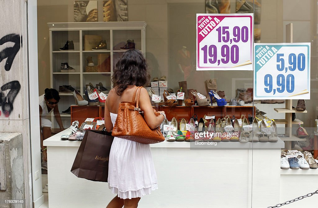 A pedestrian holds a shopping bag as she looks at the window display of a shoe store in Pescara, Italy, on Thursday, Aug. 29, 2013. Italian consumer confidence rose this month more than economists expected as households grew optimistic amid expectations that the government would cut a property tax. Photographer: Marc Hill/Bloomberg via Getty Images