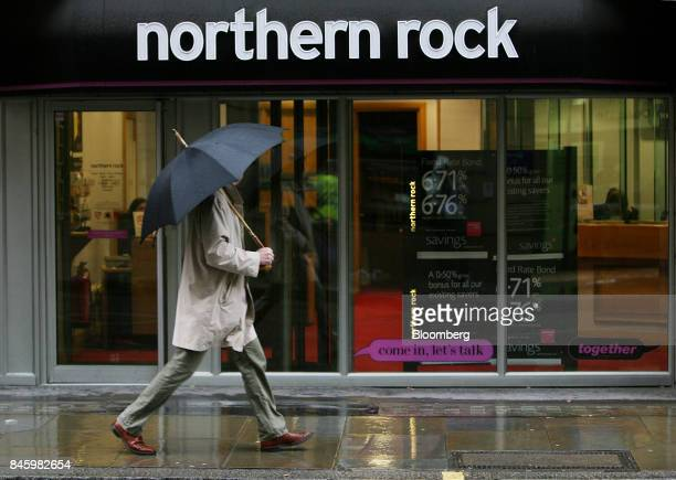 A pedestrian holds an umbrella as he shelters from the rain whilst walking past a branch of the Northern Rock Plc bank in London UK on Friday Jan 11...