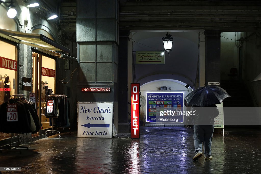 A pedestrian holds an umbrella as he walks past an outlet discount store in Naples, Italy, on Saturday, Feb. 1, 2014. In Naples, the local youth unemployment rate in 2012 was 53.6 percent compared to a national average of 35.3 percent. Photographer: Alessia Pierdomenico/Bloomberg via Getty Images