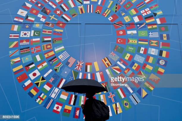 A pedestrian holds an umbrella while walking past a sign for the International Monetary Fund and World Bank Group Annual Meetings in Washington DC US...