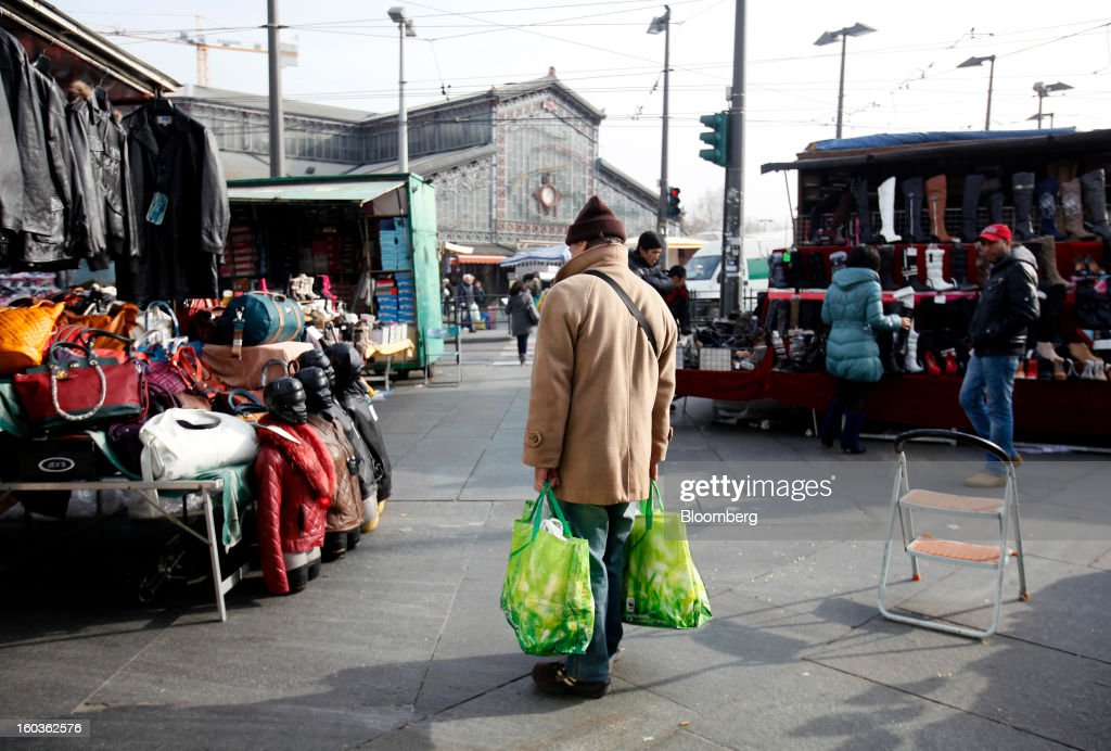 A pedestrian holds his goods in shopping bags as he stands at street market stall in Turin, Italy, on Tuesday, Jan. 29, 2013. Italy sold 8.5 billion euros ($11.4 billion) of six-month Treasury bills as rates dropped to the lowest in almost three years as the European Central Bank's pledge to buy bonds continues to provide an effective backstop even amid rising political concerns. Photographer: Alessia Pierdomenico/Bloomberg via Getty Images