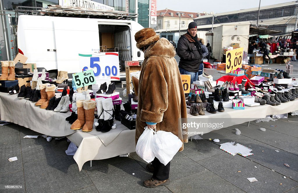 A pedestrian holds shopping bags as she browses shoes displayed for sale on a street market stall in Turin, Italy, on Tuesday, Jan. 29, 2013. Italy sold 8.5 billion euros ($11.4 billion) of six-month Treasury bills as rates dropped to the lowest in almost three years as the European Central Bank's pledge to buy bonds continues to provide an effective backstop even amid rising political concerns. Photographer: Alessia Pierdomenico/Bloomberg via Getty Images