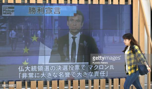 A pedestrian in central Tokyo walks by a large screen showing on May 8 a TV news broadcast of the victory of proEuropean Union centrist Emmanuel...
