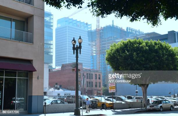 A pedestrian is dwarfed by new highrise developments October 12 2017 in downtown Los Angeles California where a construction boom has produced...