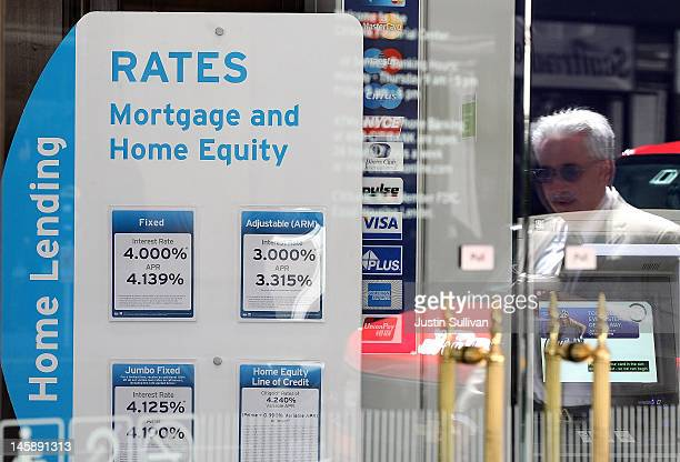A pedestrian is reflected in a window as he walks by a sign displaying mortgage rates inside a Citibank office on June 7 2012 in San Francisco...