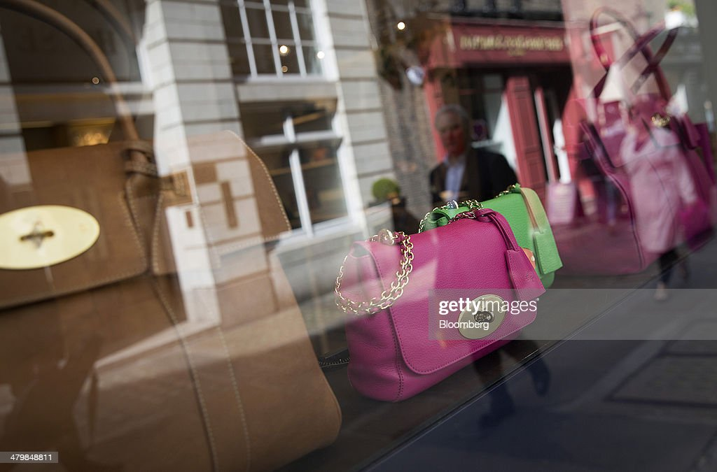 A pedestrian is reflected in the window display of a Mulberry Group Plc luxury store in London, U.K., on Thursday, March 20, 2014. Mulberry Group said Bruno Guillon will step down as chief executive officer after two years during which the British luxury handbag maker lost two-thirds of its market value. Photographer: Simon Dawson/Bloomberg via Getty Images