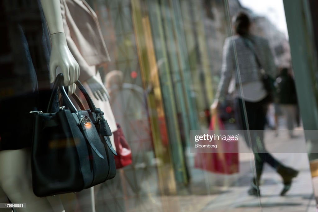 A pedestrian is reflected in the window display of a Mulberry Group Plc luxury store on New Bond Street in London, U.K., on Thursday, March 20, 2014. Mulberry Group said Bruno Guillon will step down as chief executive officer after two years during which the British luxury handbag maker lost two-thirds of its market value. Photographer: Simon Dawson/Bloomberg via Getty Images