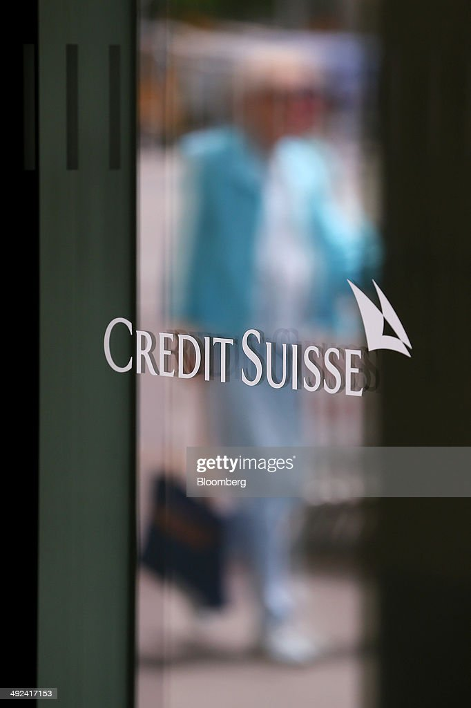 A pedestrian is reflected in the window of a Credit Suisse logo outside a Credit Suisse Group AG bank branch in Bern Switzerland on Tuesday May 20...