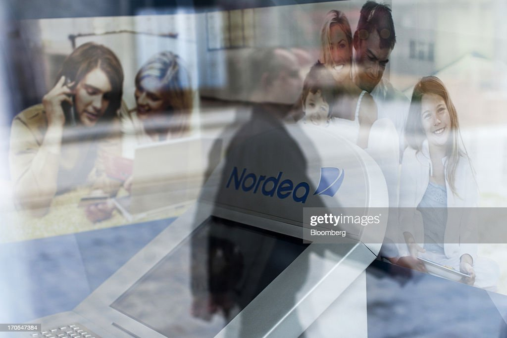 A pedestrian is reflected in the window of a Nordea Bank Polska SA bank branch in Wroclaw, Poland, on Friday, June 14, 2013. PKO Bank Polski SA, Poland's biggest lender, surged to a five-month high after signing an agreement to buy Nordea Bank AB's Polish assets to increase its dominance on the European Union's largest eastern market. Photographer: Bartek Sadowski/Bloomberg via Getty Images