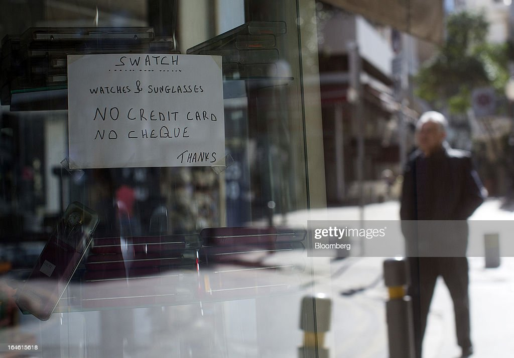 A pedestrian is reflected in the window of a store with a customer notice for cash only in Nicosia, Cyprus, on Monday, March 25, 2013. In a replay of tensions over aid for Greece at the outset of the crisis, European governments had wrangled over aid for Cyprus for nine months, exposing holes in the revamped economic management system that was built in three years of emergency policymaking, often at all-night summits. Photographer: Photographer: Simon Dawson/Bloomberg via Getty Images