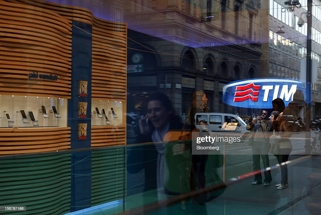 A pedestrian is reflected in the window of a TIM store, the mobile unit of Telecom Italia SpA, as she uses her mobile phone in Milan, Italy, on Tuesday, Nov. 20, 2012. Telecom Italia SpA said it is still reviewing the possible spinoff of its fixed-line network and the company's board will discuss the outcome of its analysis on Dec. 6. Photographer: Alessia Pierdomenico/Bloomberg via Getty Images