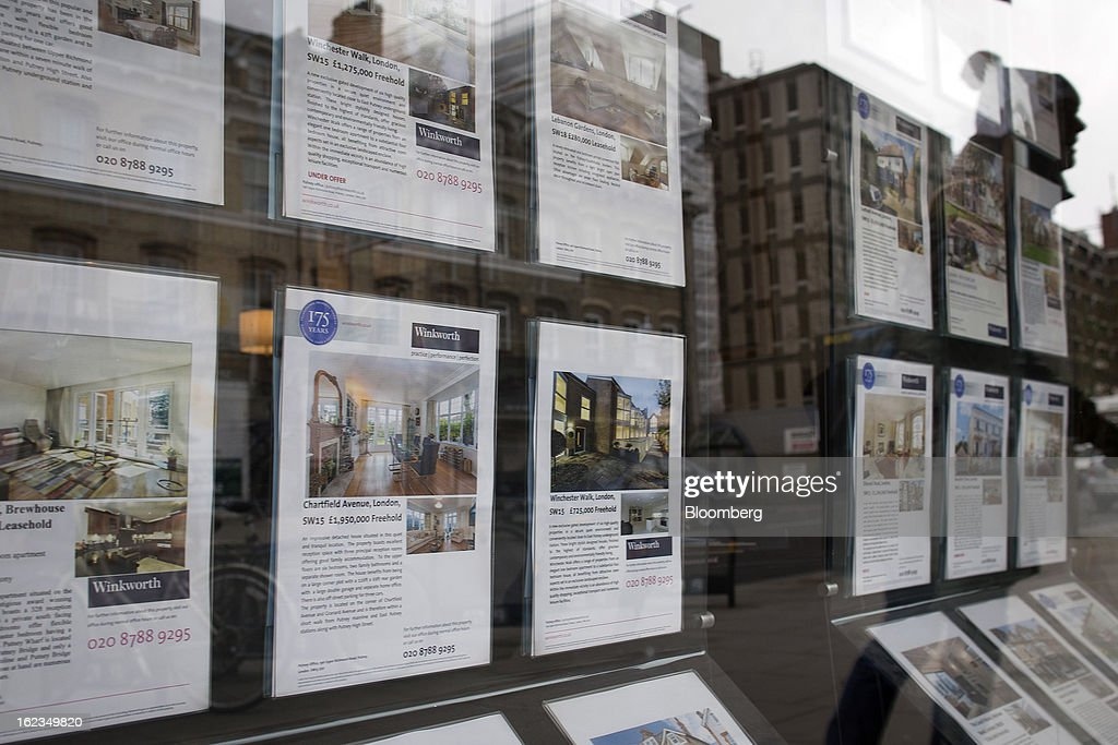 A pedestrian is reflected in the window of an estate agent as they look at residential homes advertised in the Putney district of London, U.K., on Friday, Feb. 22, 2013. U.K. home sellers raised their asking prices to the most for a February in five years as inquiries from potential buyers increased, Rightmove Plc said. Photographer: Simon Dawson/Bloomberg via Getty Images