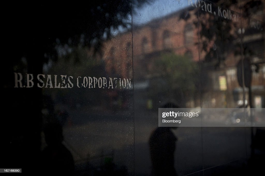 A pedestrian is reflected on a wall with R.B. Sales Corp. signage in Kolkata, India, on Tuesday, Feb. 19, 2013. India's slowest economic expansion in a decade is limiting profit growth at the biggest companies even as foreigners remain net buyers of the nation's stocks, according to Kotak Institutional Equities. Photographer: Brent Lewin/Bloomberg via Getty Images
