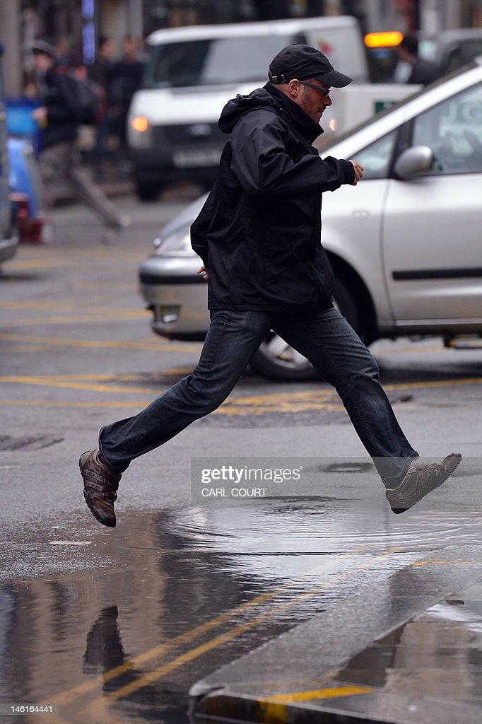 A pedestrian jumps over a puddle left by persistent rain in central London on June 11, 2012. Persistent rainfall over much of southern England and the midlands has lead to the risk of flooding with the Met office issuing a severe weather warning.