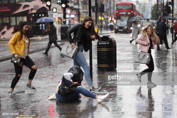 A pedestrian lands on the pavement after trying to leap over a puddle as rain fell in central London on August 9 2017 / AFP PHOTO / Tolga AKMEN