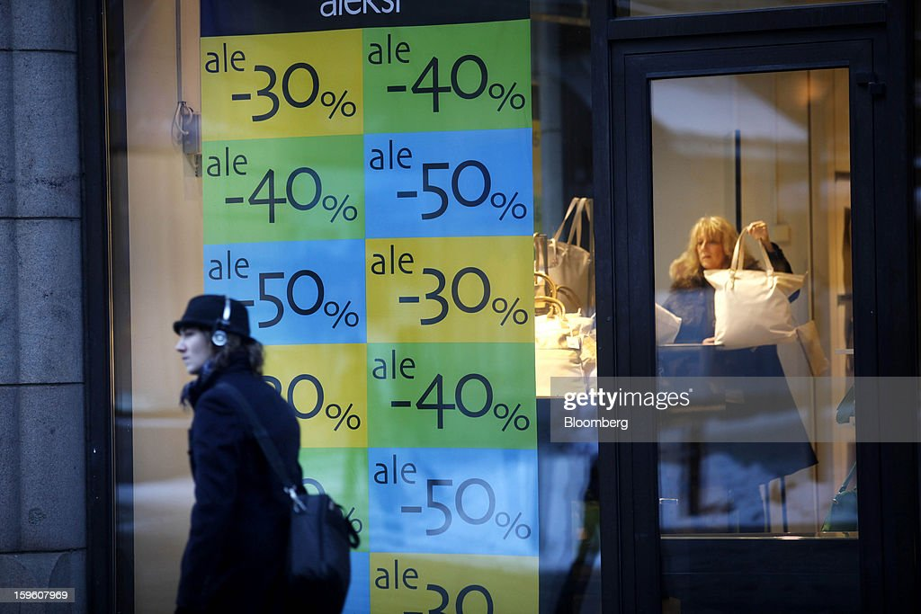 A pedestrian listens to headphones as she passes the window of a store advertising sale price discounts in Helsinki, Finland, on Thursday, Jan. 17, 2013. Pedestrians pass a display of mobile phones in the window of a Nokia Oyj store in Helsinki, Finland, on Thursday, Jan. 17, 2013. The pace of Finland's debt growth is alarming and the country must undertake economic reforms together with reining in spending, Finnish Prime Minister Jyrki Katainen said in an op-ed piece published in newspaper Savon Sanomat. Photographer: Ville Mannikko/Bloomberg via Getty Images