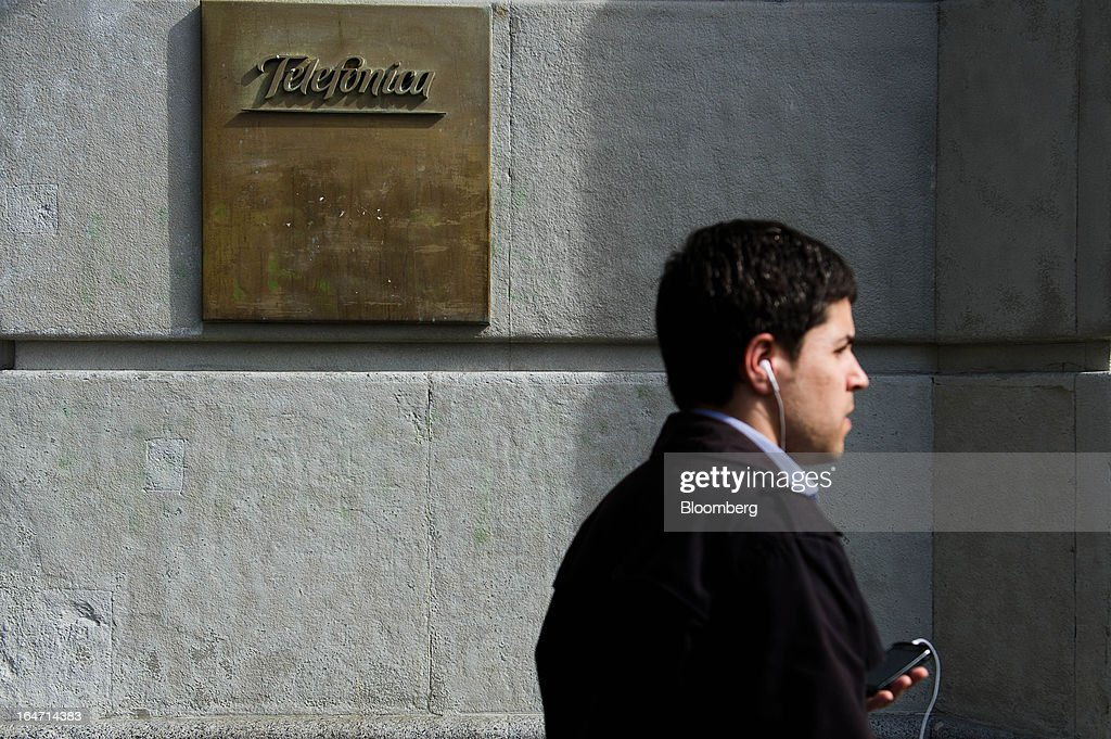 A pedestrian listens to headphones while passing a Telefonica SA plaque outside the Mobile World Centre building in Barcelona, Spain, on Tuesday, March 26, 2013. Telefonica, seeking to reduce net debt by more than 4 billion euros this year, is following companies such as Repsol SA, Spain's biggest oil company, and builder Actividades de Construccion & Servicios SA, to sell treasury shares. Photographer: David Ramos/Bloomberg via Getty Images