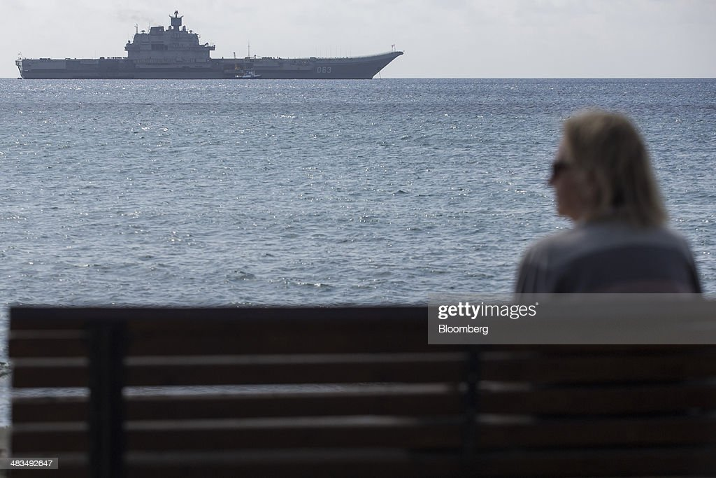 A pedestrian looks across the Mediterranean Sea towards the Russian Navy's Kremi class aircraft carrier Admiral Kuznetsov as it stands offshore in Limassol, Cyprus, on Tuesday, April 8, 2014. Cyprus wants to shield financial flows with Russia, where it's the biggest foreign investor, as the U.S. and the European Union ratchet up sanctions in response to President Vladimir Putin's annexing Crimea from Ukraine. Photographer: Andrew Caballero-Reynolds/Bloomberg via Getty Images