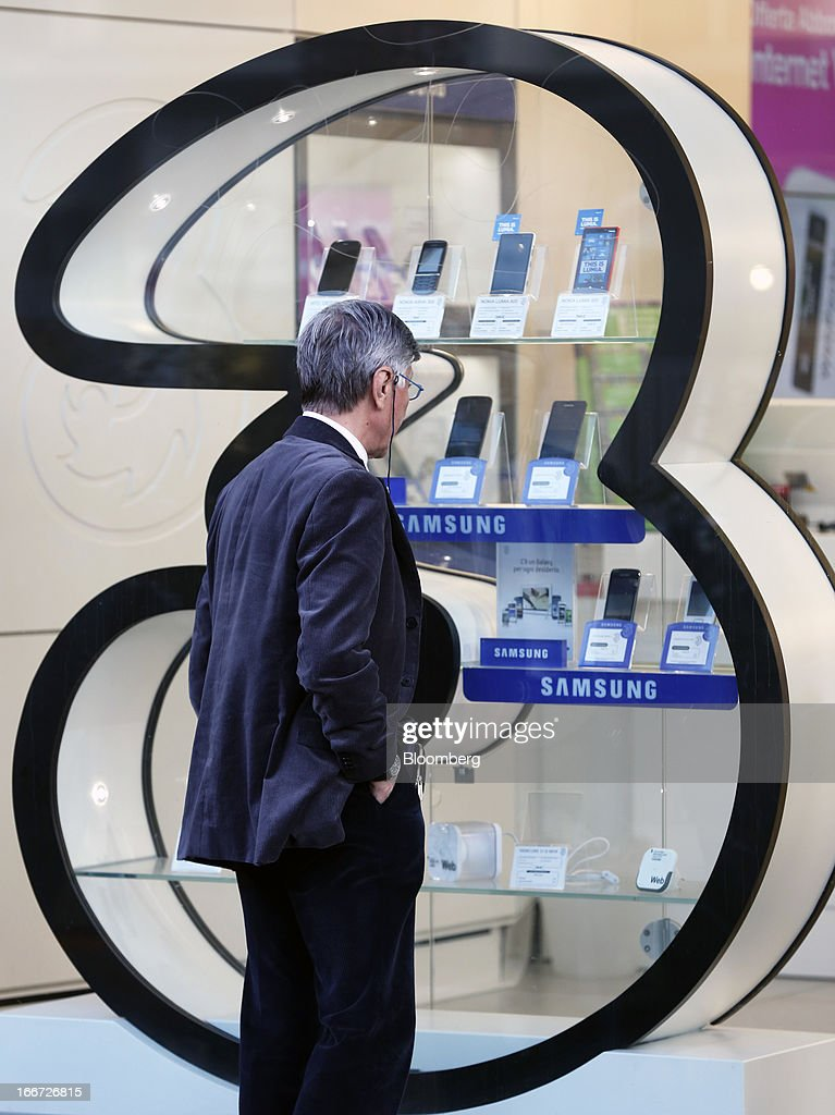 A pedestrian looks at a display of Samsung Electronics Co. smartphones in the window display of a 3 Italia mobile phone store in Rome, Italy, on Monday, April 15, 2013. Telecom Italia SpA, which received approval from its board to pursue a possible merger with Hutchison Whampoa Ltd.'s Italian business 3 Italia, said billionaire Li Ka-shing's company would want control of any combined entity. Photographer Alessia Pierdomenico/Bloomberg via Getty Images