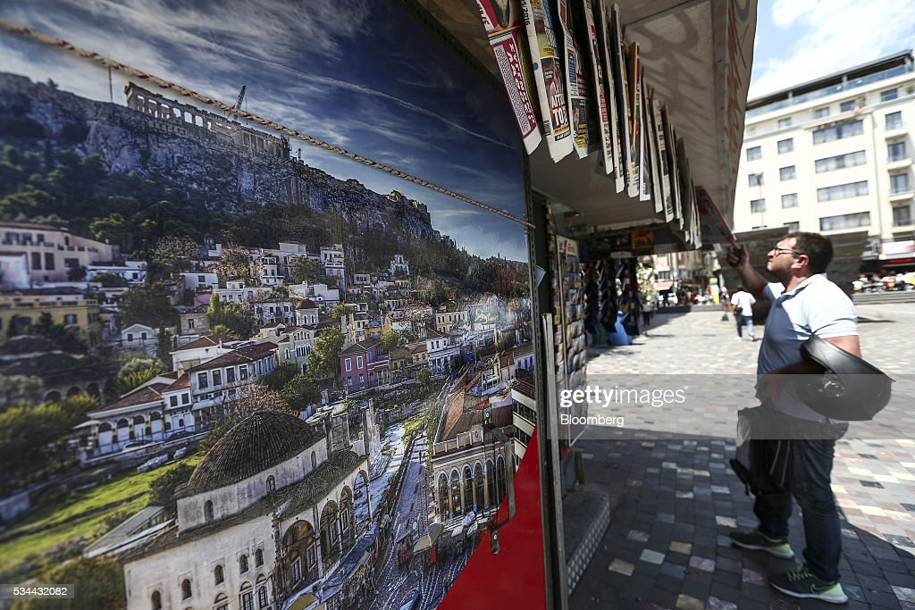 A pedestrian looks at a newspaper hanging outside a magazine kiosk decorated with a city scene in Athens, Greece, on Thursday, May 26, 2016. Greece may have passed a milestone and its bond market has been lucrative for some investors, but the road to recovery doesn't look much shorter. Photographer: Yorgos Karahalis/Bloomberg via Getty Images