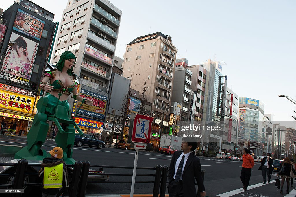A pedestrian looks at a promotional statue displayed by the side of a road in the district of Akihabara in Tokyo, Japan, on Wednesday, Feb. 13, 2013. Japan's economy unexpectedly shrank last quarter as falling exports and a business investment slump outweighed improved consumption, highlighting the challenge facing Prime Minister Shinzo Abe as he seeks to end deflation. Photographer: Noriko Hayashi/Bloomberg via Getty Images