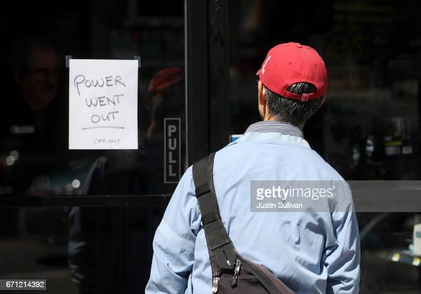 A pedestrian looks at a sign posted on the door of a hardware store during a citywide power outage on April 21 2017 in San Francisco California...