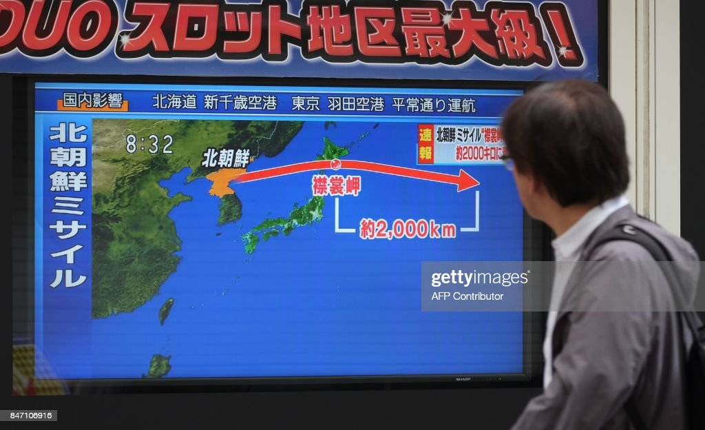 A pedestrian looks at a television screen displaying a map of Japan (R) and the Korean Peninsula in Tokyo on September 15, 2017, following a North Korean missile test that passed over Japan. North Korea fired an intermediate range ballistic missile eastwards over Japan and into the Pacific on September 15, the US said, its latest provocation amid high tensions over its banned weapons programmes. / AFP PHOTO / Kazuhiro NOGI