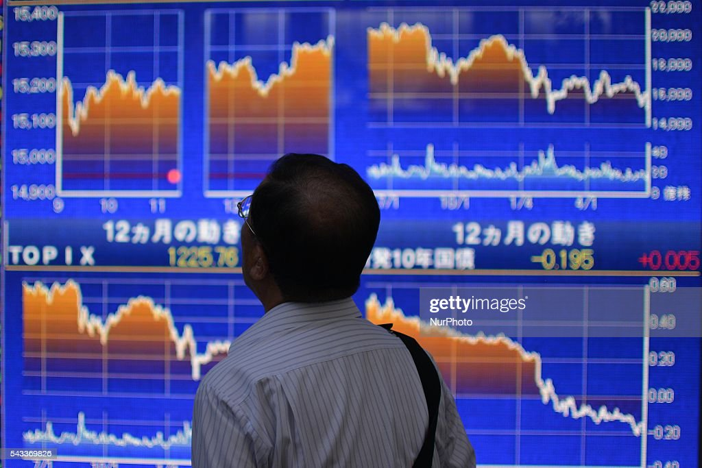 A pedestrian looks at an electronic board showing the stock market indices of various countries outside a brokerage in Tokyo, Japan, June 27, 2016. Monday as markets struggled to shake off deep uncertainty sparked by Britainfs decision to leave the EU.