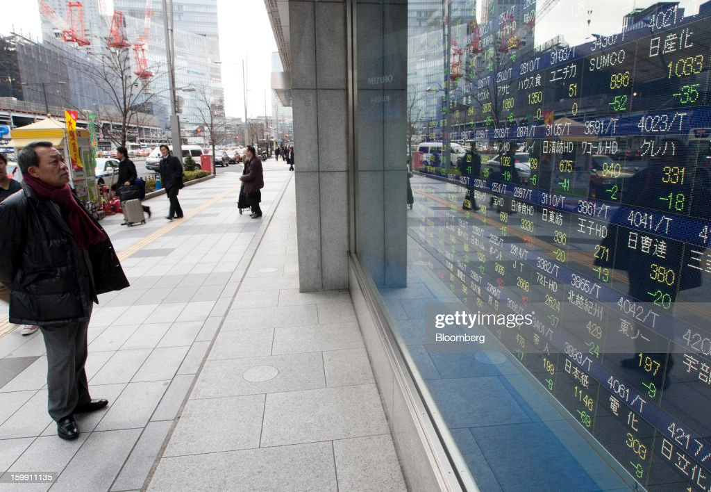 A pedestrian looks at an electronic stock board outside a securities firm in Tokyo, Japan, on Wednesday, Jan. 23, 2013. Japan shares declined, with the Nikkei 225 Stock Average posting its first three-day decline since elections were called, as the yen climbed after the Bank of Japan said it will wait a year to add open-ended stimulus. Photographer: Tomohiro Ohsumi/Bloomberg via Getty Images