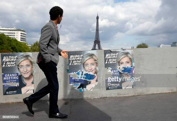A pedestrian looks at campaign posters of Marine Le Pen French National Front and political party leader one of the eleven candidates who runs in the...