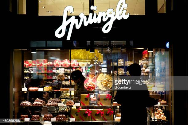 A pedestrian looks at chocolate in the illuminated window display of a Lindt Spruengli AG store in Zurich Switzerland on Thursday Dec 11 2014 The...