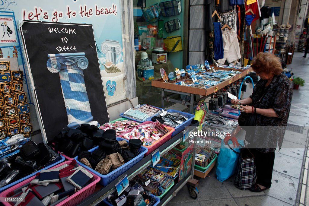 A pedestrian looks at compact discs for sale at a street stall displaying a 'Welcome to Greece' sign in Athens, Greece, on Saturday, Aug. 10, 2013. Greece's economy contracted for a 20th quarter, extending an economic slump that has left more than six in 10 young Greeks out of work. Photographer: Angelos Tzortzinis/Bloomberg via Getty Images