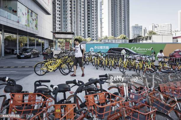 A pedestrian looks at his smartphone while walking from a designated bicycle parking space in Shanghai China on Thursday Sept 12 2017 Across Chinese...