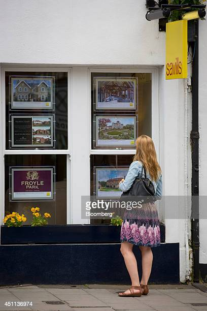A pedestrian looks at information leaflets of residential properties displayed for sale in the window of a Savills estate agents in Guildford UK on...