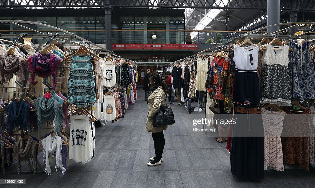 A pedestrian looks at items of clothing displayed for sale on a clothes stall at Old Spitalfields Market in London, U.K., on Wednesday, May 29, 2013. Annual U.K. consumer-price inflation slowed to 2.4 percent last month from 2.8 percent in March, the Office for National Statistics said May 21. Photographer: Chris Ratcliffe/Bloomberg via Getty Images
