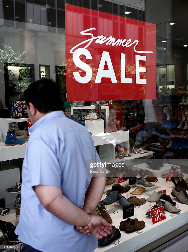 A pedestrian looks at men's shoes in the window of a store advertising a summer sale in Athens, Greece, on Friday, Aug. 9, 2013. Greece's economy contracted for a 20th quarter, extending an economic slump that has left more than six in 10 young Greeks out of work. Photographer: Angelos Tzortzinis/Bloomberg via Getty Images