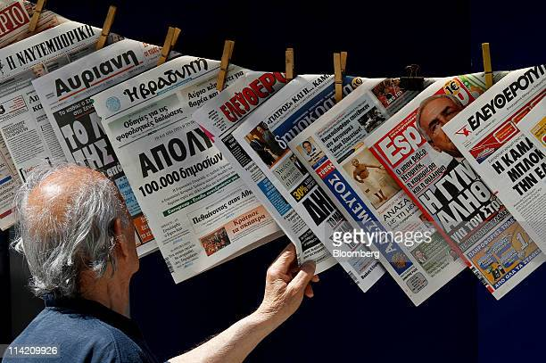 A pedestrian looks at newspaper headlines hanging from a kiosk in Athens Greece on Monday May 16 2011 International Monetary Fund chief Dominique...