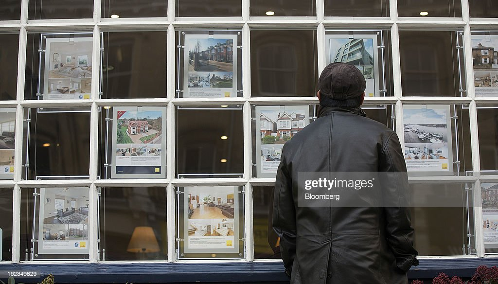 A pedestrian looks at residential houses and apartments advertised in the window on an estate agent in the Putney district of London, U.K., on Friday, Feb. 22, 2013. U.K. home sellers raised their asking prices to the most for a February in five years as inquiries from potential buyers increased, Rightmove Plc said. Photographer: Simon Dawson/Bloomberg via Getty Images