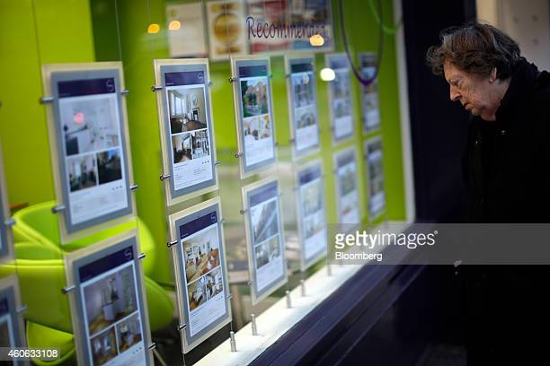 A pedestrian looks at residential property information leaflets displayed in the window of an estate agent in the Putney district of London UK on...
