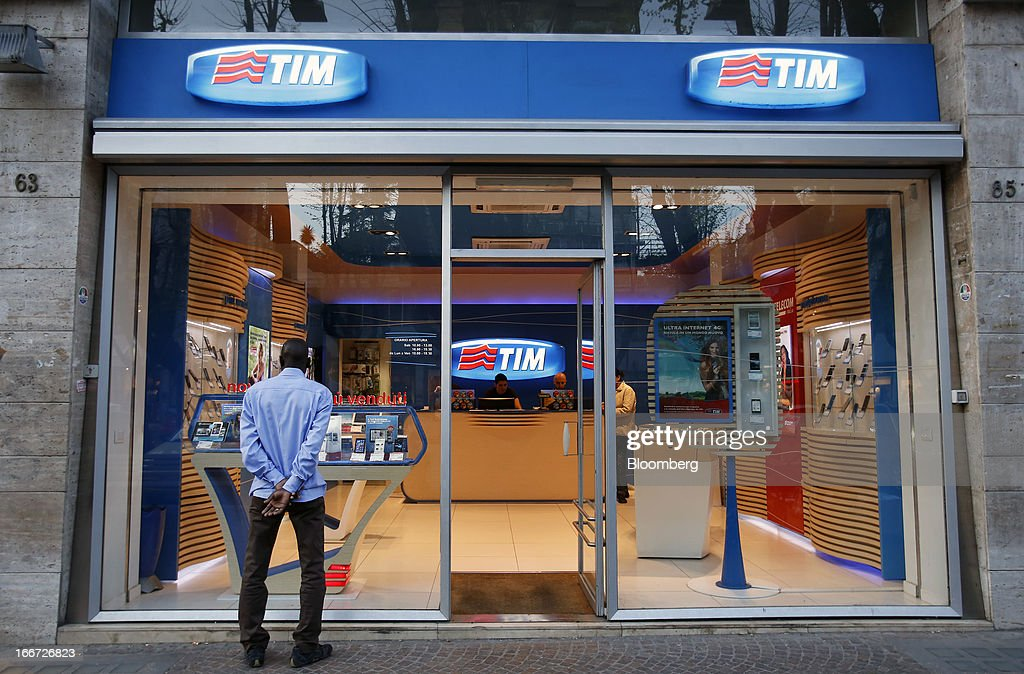 A pedestrian looks at smartphones displayed in the window of a TIM store, the mobile phone unit of Telecom Italia SpA in Rome, Italy, on Monday, April 15, 2013. Telecom Italia SpA, which received approval from its board to pursue a possible merger with Hutchison Whampoa Ltd.'s Italian business 3 Italia, said billionaire Li Ka-shing's company would want control of any combined entity. Photographer Alessia Pierdomenico/Bloomberg via Getty Images