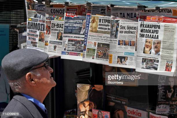 A pedestrian looks at the Dominique StraussKahn headlines on a newspaper hanging from a kiosk in Athens Greece on Monday May 16 2011 International...