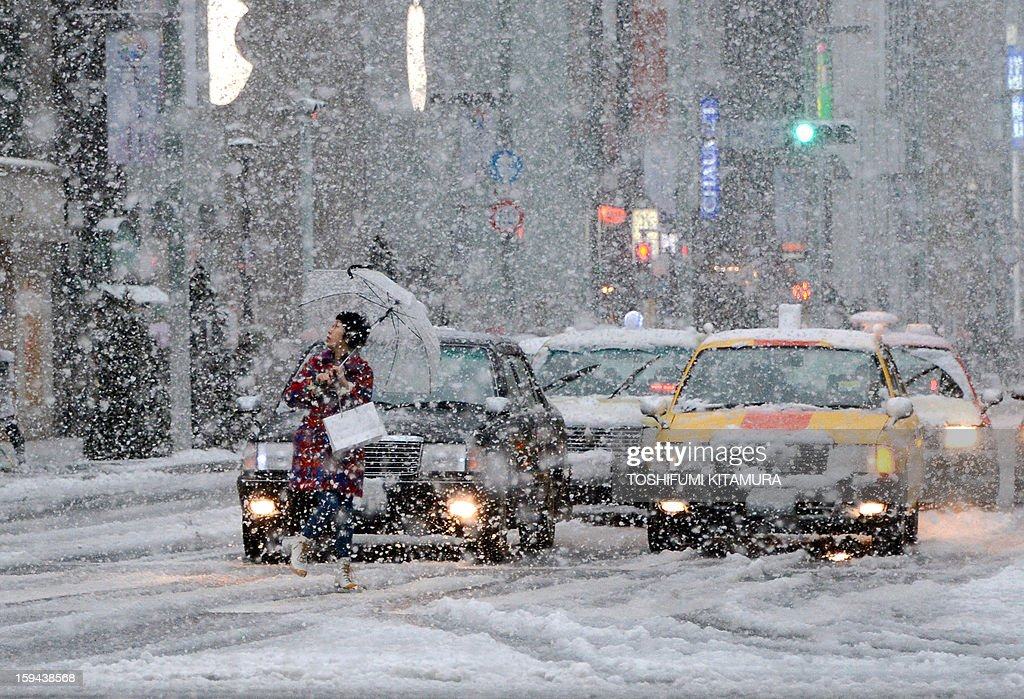 A pedestrian (L) looks at the falling snow while crossing the road in the Ginza shopping district in Tokyo on January 14, 2013. A storm system grasped central Japan on January 14, causing heavy snow fall around the Japanese capital. AFP PHOTO / TOSHIFUMI KITAMURA