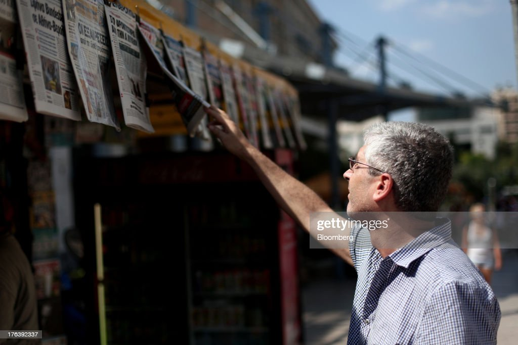 A pedestrian looks at the front page of a newspaper hanging outside a street kiosk in Athens, Greece, on Monday, Aug. 12, 2013. Greece's economy contracted for a 20th quarter, extending an economic slump that has left more than six in 10 young Greeks out of work. Photographer: Angelos Tzortzinis/Bloomberg via Getty Images